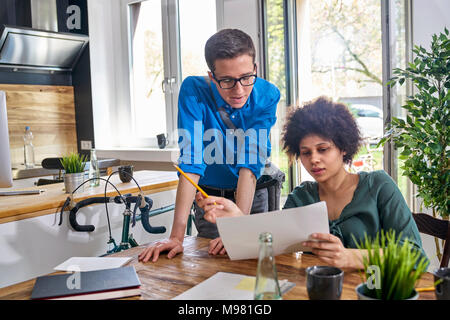 Two colleagues discussing paper in modern office - Stock Photo