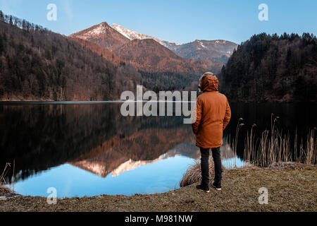 Austria, St. Gilgen, Krottensee, young man wearing winter jacket - Stock Photo