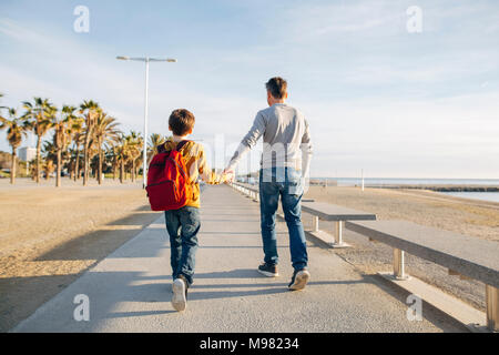 Father and son walking on beach promenade - Stock Photo