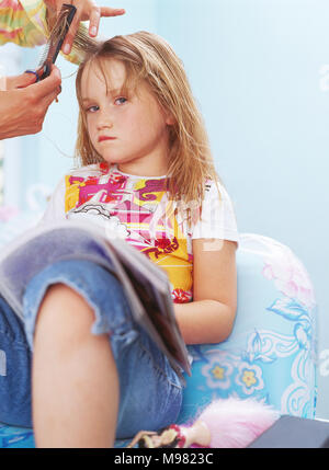 Hands of hairdresser combing and cutting hair of unhappy little girl - Stock Photo