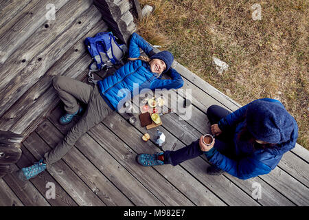 Overhead view of couple hikers having a break at mountain hut - Stock Photo
