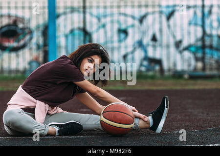 Young woman with basketball stretching on outdoor court - Stock Photo