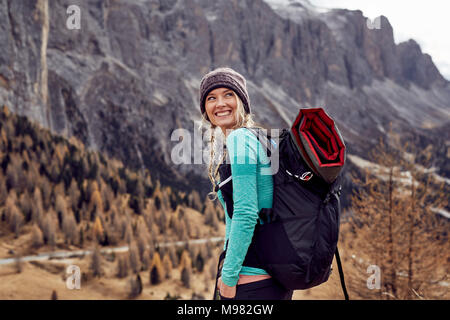 Portrait of happy young woman hiking in the mountains - Stock Photo