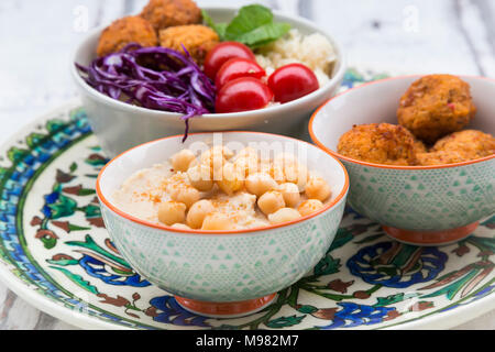 Hummus, sweet potato balls, Couscous and vegetables in bowls - Stock Photo