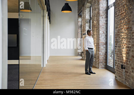 Mature businessman standing at the window in modern office - Stock Photo