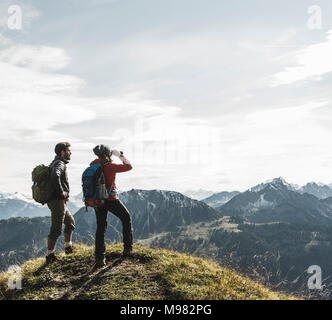 Austria, Tyrol, young couple standing in mountainscape looking at view - Stock Photo