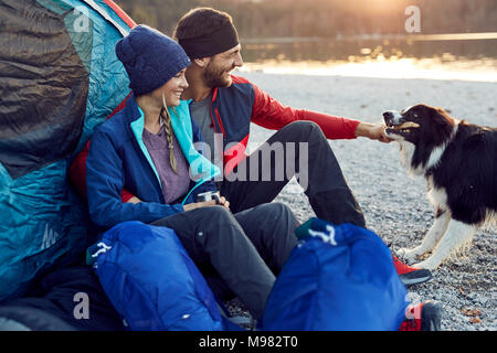 Happy young couple with dog sitting at tent at lakeshore - Stock Photo
