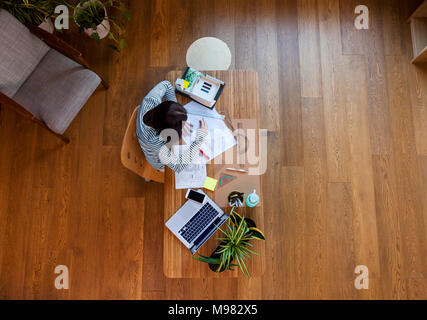 Young architect working in office, from directly above - Stock Photo