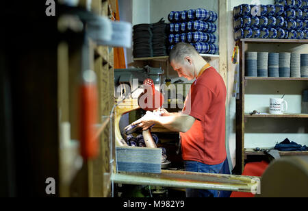 Shoemaker working on slippers in workshop - Stock Photo
