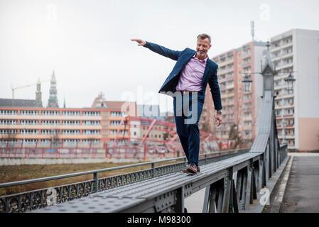 Stylish mature businessman wearing blue suit balancing on railing of bridge - Stock Photo