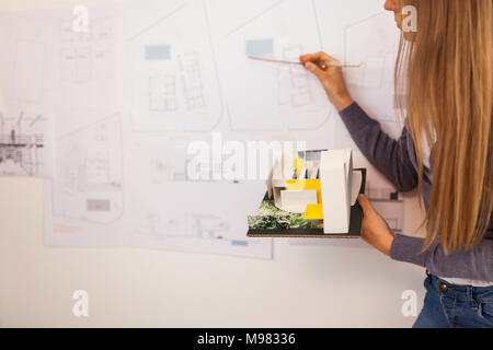 Female architect working on a project, holding architectural model - Stock Photo