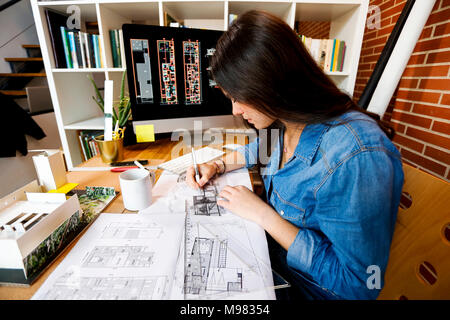 Young woman working in architecture office, drawing blueprints - Stock Photo