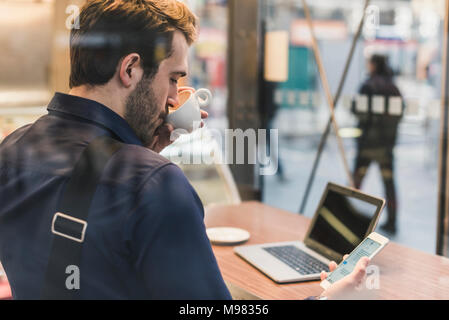 Young businessman in a cafe at train station with cell phone drinking coffee from cup - Stock Photo