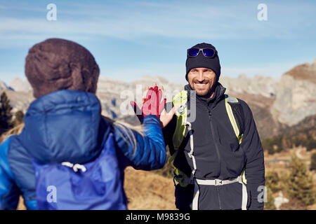 Smiling man and woman hiking in the mountains high fiving - Stock Photo