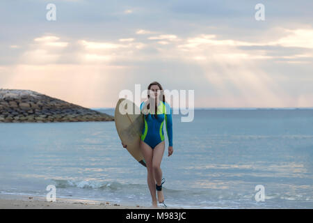 Indonesia, Bali, young woman with surf board walking at beach - Stock Photo
