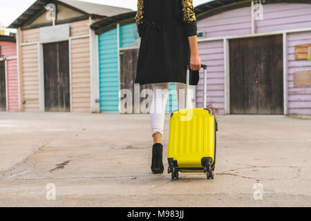 Back view of walking woman with yellow trolley bag, partial view - Stock Photo