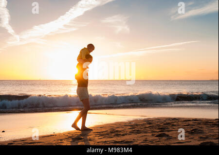 Mother walking with little daughter on the beach at sunset - Stock Photo
