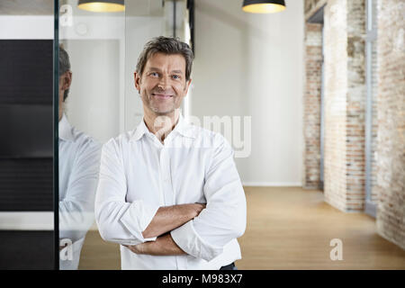 Portrait of smiling businessman leaning against glass pane in modern office - Stock Photo