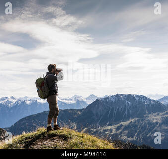 Austria, Tyrol, young man standing in mountainscape looking at view with binoculars - Stock Photo