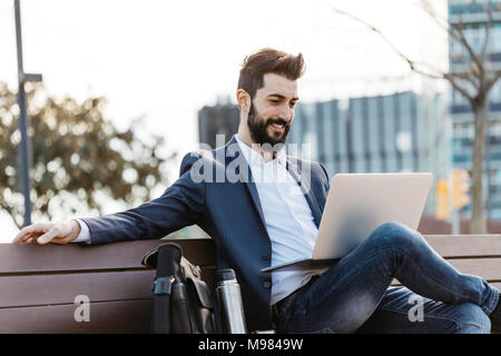 Businessman sitting on bench outside office building using laptop - Stock Photo