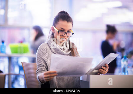 Portrait of young woman working in an office - Stock Photo