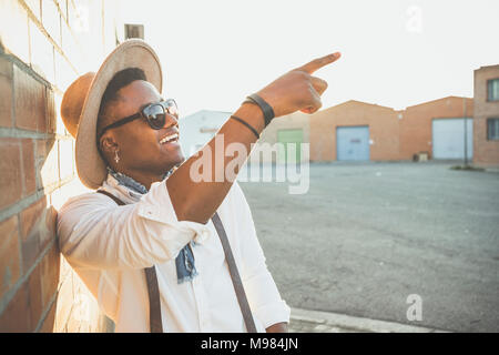 Portrait of laughing young man wearing hat and sunglasses  pointing on something - Stock Photo