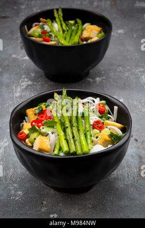 Bowl of vegan Pad Thai with mini green asparagus and tofu, chili, spring onion, peanut and coriander - Stock Photo