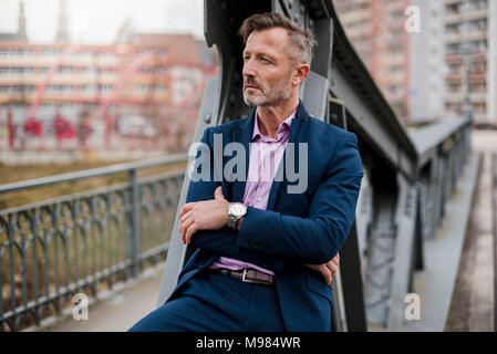 Portrait of stylish mature businessman wearing blue suit - Stock Photo