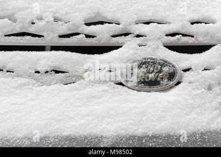 Snow covered Land Rover badge - Stock Photo