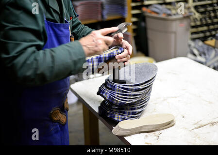 Close-up of shoemaker working on slippers in workshop - Stock Photo