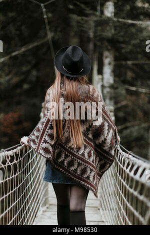 Back view of fashionable young woman wearing hat and poncho walking on suspension bridge - Stock Photo
