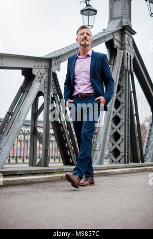 Stylish mature businessman wearing blue suit walking on bridge - Stock Photo