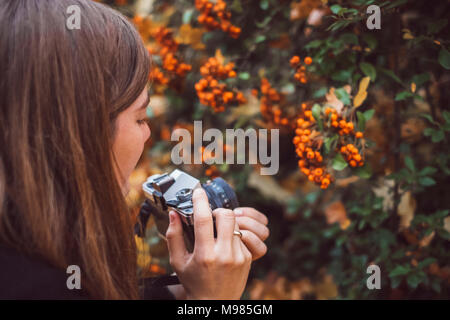 Young woman taking photos with old camera in autumnal nature - Stock Photo