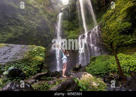 Indonesia, Bali, young woman standing at Sekumpul waterfall - Stock Photo
