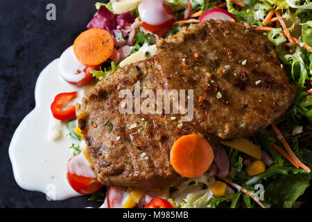 Veggie burger with lettuce, vegetables and yoghurt sauce - Stock Photo
