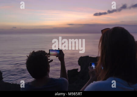 Indonesia, Bali, Lembongan island, friends at ocean coast at dusk taking cell phone pictures - Stock Photo