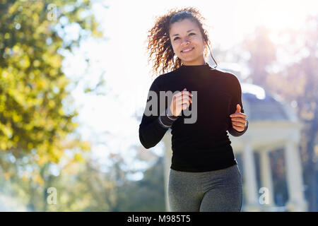 Smiling young woman with earphones running in park - Stock Photo