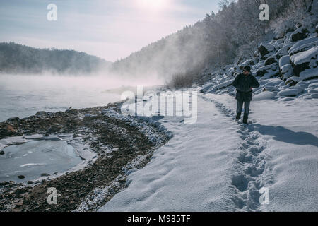 Russia, Amur Oblast, man walking at riverside of Bureya in snow-covered nature - Stock Photo