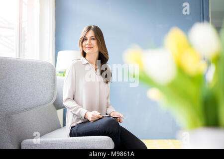 Portrait of smiling woman sitting on couch holding tablet - Stock Photo