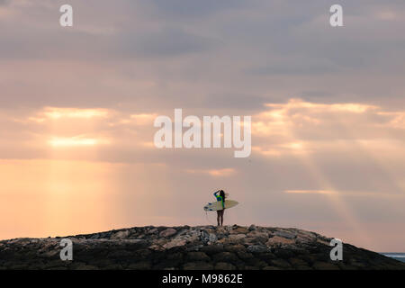 Indonesia, Bali, young woman with surf board in the evening - Stock Photo