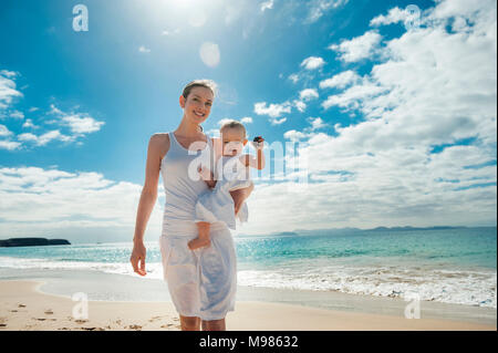 Mother walking with little daughter on the beach - Stock Photo