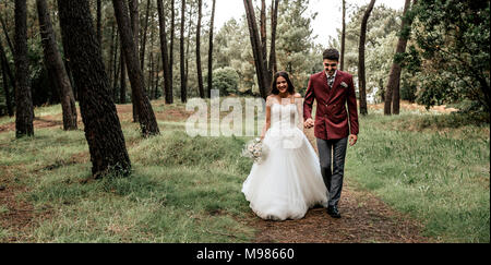 Happy bride and groom walking in forest - Stock Photo