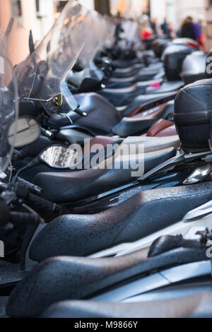 Vespas and other motorcycles on Rome cobbled streets, Lazio, Italy. - Stock Photo