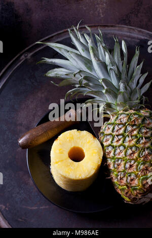 Stack of pineapple slices, whole pineapple and cleaver - Stock Photo
