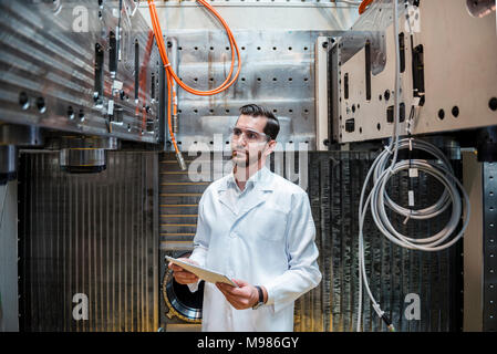 Man wearing lab coat and safety goggles at machine holding tablet - Stock Photo