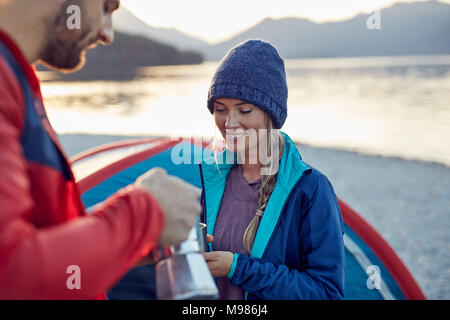 Young couple at tent having coffee break - Stock Photo