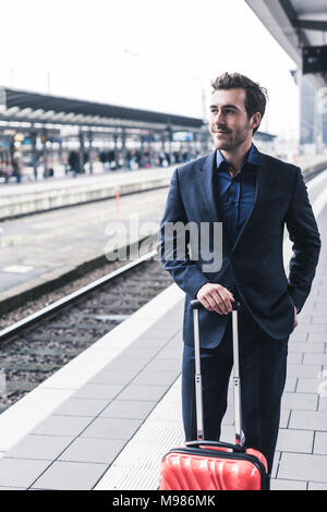 Young businessman waiting at station platform - Stock Photo