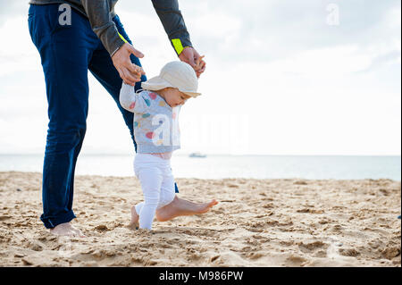 Spain, Lanzarote, baby girl walking on the beach with the help of his father - Stock Photo
