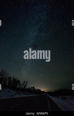 Russia, Amur Oblast, empty country road under starry sky in winter - Stock Photo