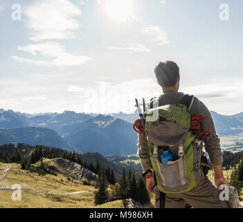 Austria, Tyrol, young man in mountainscape looking at view - Stock Photo